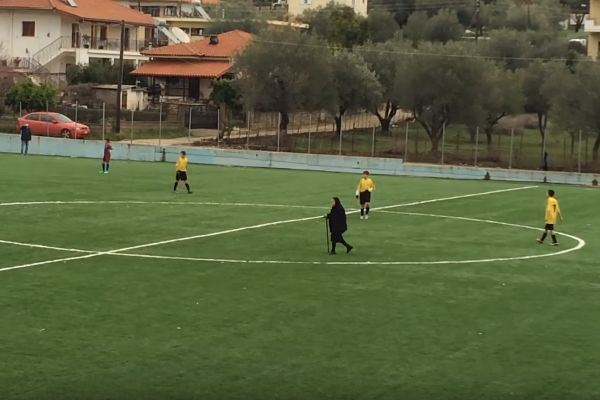 An elderly lady walks across the pitch during a youth match in Greece