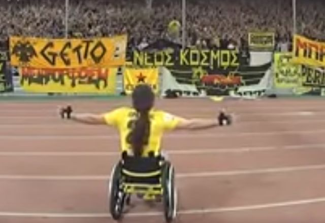 Fan in wheelchair leads AEK Athens chants in front of a packed stand of supporters