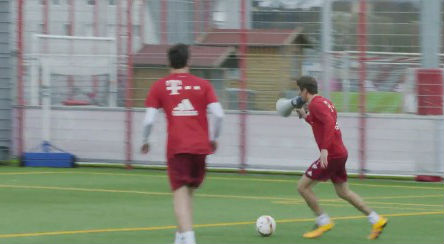 Thomas Müller commentates through a megaphone while scoring a goal during a Bayern Munich training session