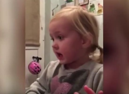 A two-year-old sings Arsenal songs while sitting at the kitchen table in her high chair