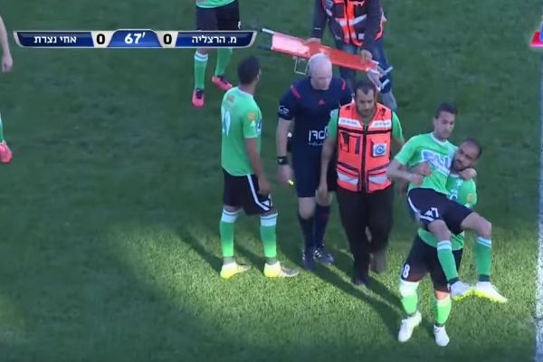 Player carries team-mate off the pitch after he was dropped from a stretcher during a match in Israel