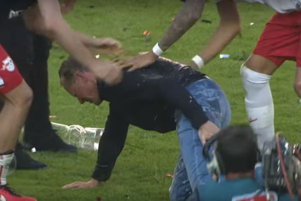 RB Leipzig manager Ralf Rangnick gets an injury running away from beer shower after their promotion