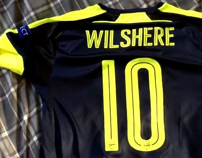 An Arsenal fan throws his Jack Wilshere shirt out the window