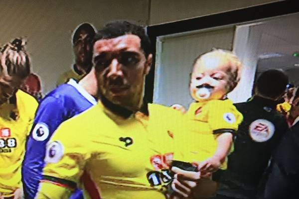 Troy Deenet holds a baby Watford mascot with moustache dummy before 3-1 win against Manchester United