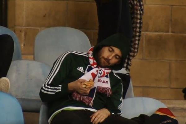 An Osasuna fan eats large sandwich, sleeps and dances at Real Sociedad