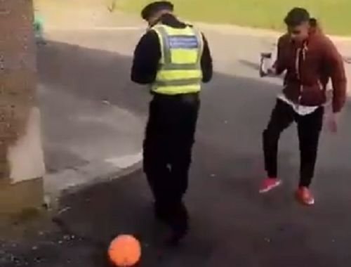 Youth nutmegs police community support officer by the side of a road in Bradford