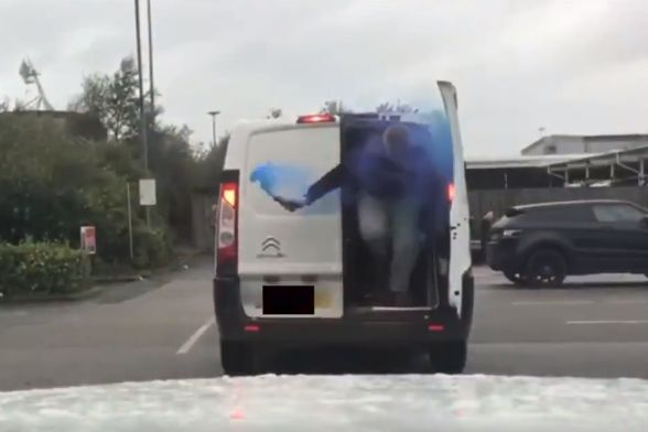 Bolton fans exit a van after lighting a blue flare inside on their way to a game against QPR