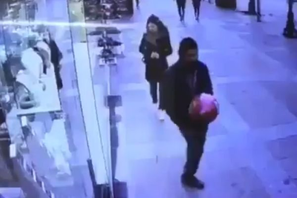 A man attempts to overhead kick a red balloon on the pavement