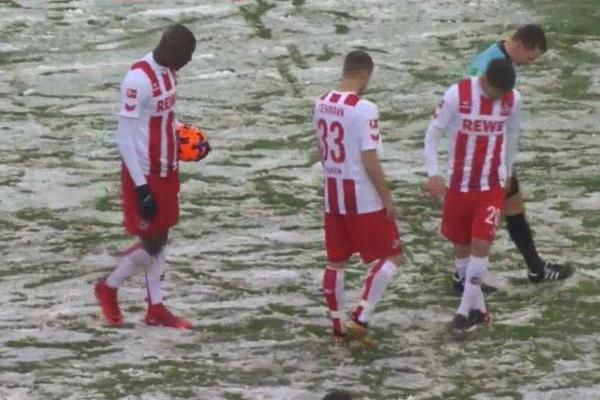 The players and referee can't find the penalty spot in the snow during Cologne 3-4 Freiburg