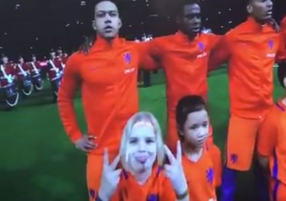 Young Netherlands mascot makes face at camera during anthems before England friendly