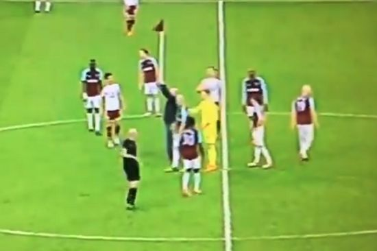 West Ham fan raises a corner flag in the centre circle during 0-3 defeat to Burnley at the London Stadium
