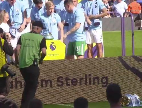 Oleksandr Zinchenko knocks over Manchester City's Premier League trophy