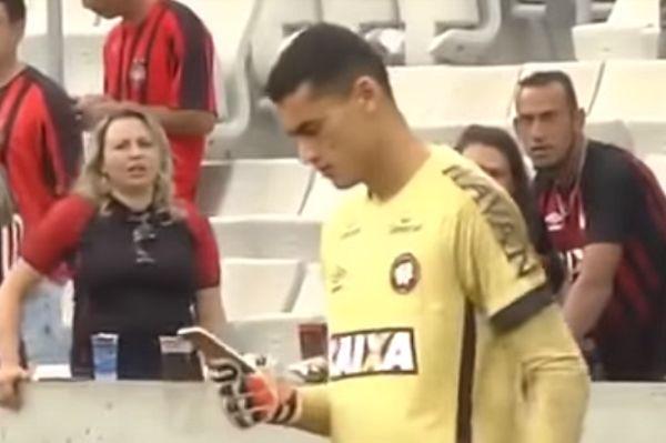 Atlético Paranaense goalkeeper Santos checks phone during match