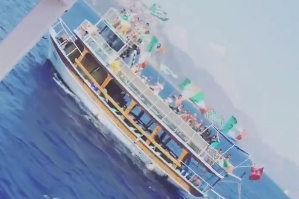 A boat of Celtic fans sail past a boat of Rangers fans off the coast of Turkey
