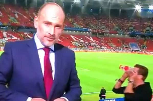 A fan with cups over his eyes walks behind a reporter at Colombia v England in the last 16 of the World Cup in Russia