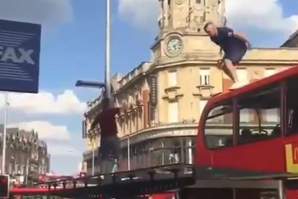 An England fan jumps off a London double-decker bus and crashes through the roof of a bus stop