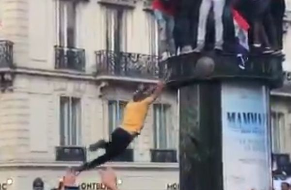 France fan falls trying to jump onto an advertising column during street celebrations of World Cup win