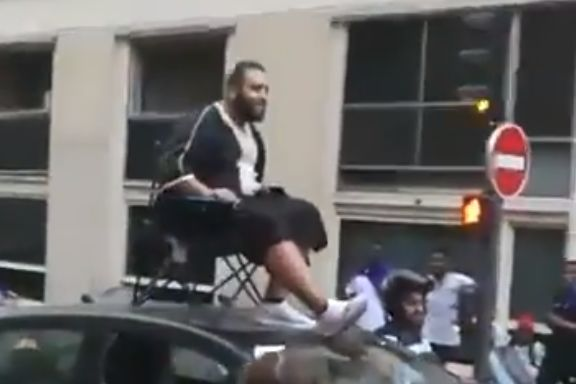A France fan sitting on a chair on the roof of a car driving around Paris after they won the World Cup in Russia