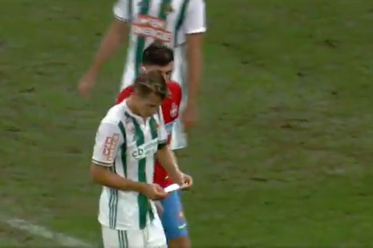 Steaua's Raul Rusescu grabs a Rapid Vienna tactics note from the bench in a Europa League game