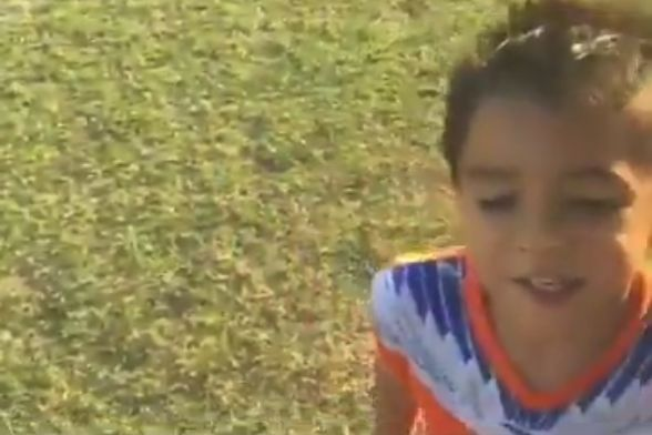 A young boy stops playing in a match to ask for food after seeing Cheetos