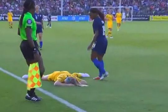 Australia women's Ellie Carpenter after being hit in the face by the ball in a match against USA