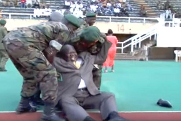 Ugandan deputy prime minister Moses Ali kicks a ball and falls over at the national stadium