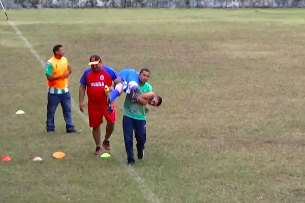 An injured player is carried off the pitch by different people in a Campeonato Amazonense Under-17 match in Brazil