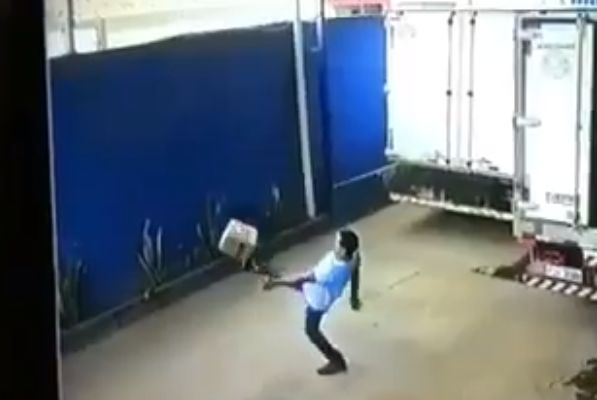 Man does kick-ups with cardboard box before volleying it back into lorry