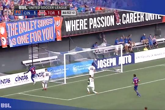 Cincinnati's Fanendo Adi falls over the advertising hoardings after scoring against Toronto in a USL game