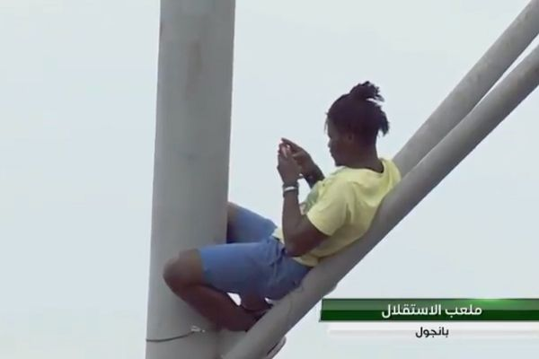 A fan climbs a tower at Independence Stadium to watch an Africa Cup of Nations qualifier between Gambia and Algeria