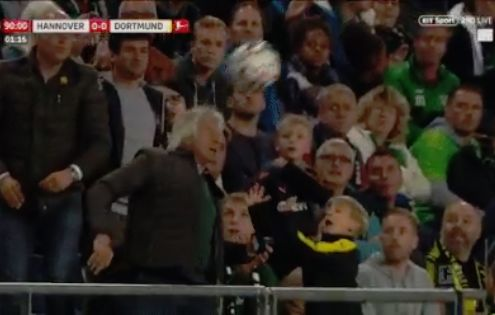 A fan heads the ball back and trips over a child during Hannover 96 0-0 Borussia Dortmund at HDI Arena