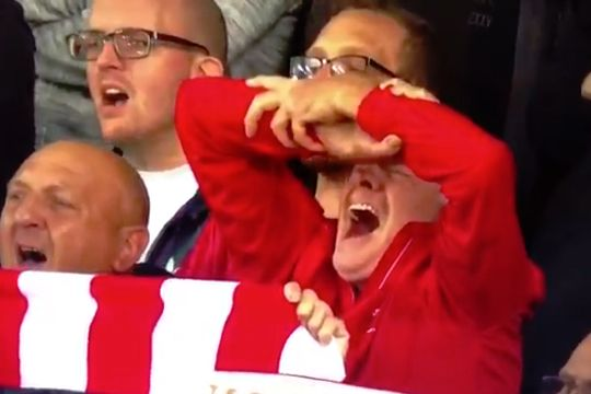 Liverpool fan crosses his arms in place of a scarf while singing You'll Never Walk Alone at Anfield before clash with PSG