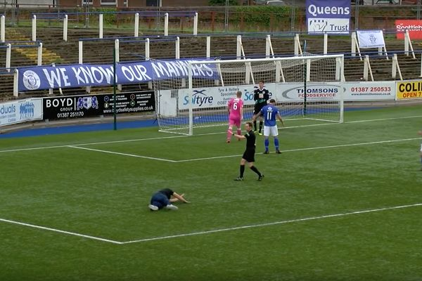 A pitch invader trips over in the area as Stephen Dobbie takes a penalty for Queen of the South in a 5-0 win over Ayr at Palmerston Park
