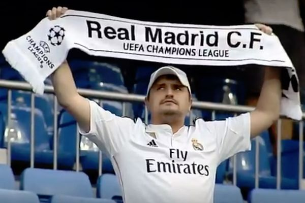 A Real Madrid poses with his scarf at the Bernabéu and has his photo retaken