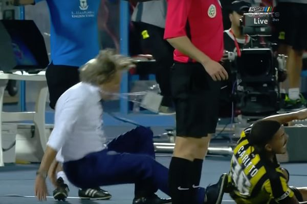 An Al-Ittihad player runs into Al-Hilal manager Jorge Jesus, who falls over