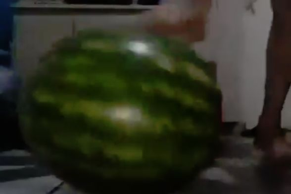 Someone trips as they attempt to kick a melon in their room