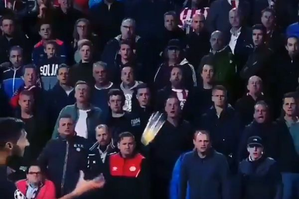 Inter's Matteo Politano catches a beer thrown at him by PSV Eindhoven fans