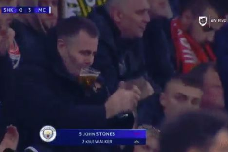 A Shakhtar Donetsk fan holds his cup of beer between his lips while applauding during their 0-3 Champions League defeat to Man City