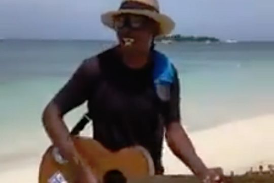 Man with guitar on a beach sings Sh*t on the Villa for a Birmingham City fan in Jamaica