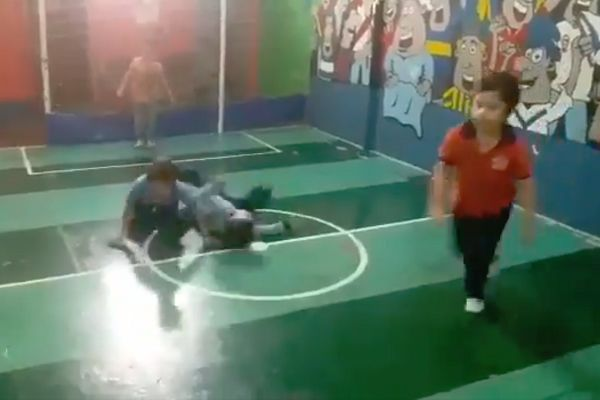Sliding tackle in an indoor kids game on a mini pitch