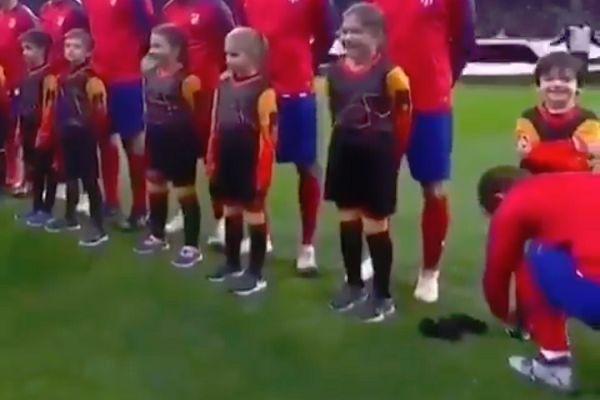 Antoine Griezmann ties a mascot's laces before Atlético Madrid vs Monaco in the Champions League
