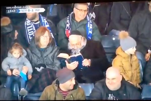Israel fan reads the Chumash, the Torah in printed form, during the 3-2 Nations League defeat to Scotland