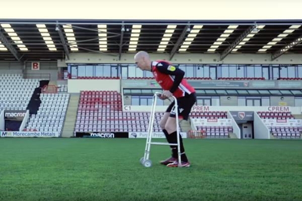 Morecambe's Kevin Ellison uses a walker to mock his FIFA speed rating