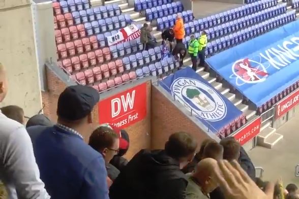 "Leeds fans sing ""You don't know what you're doing"" to Wigan supporters trying to untie their flag"