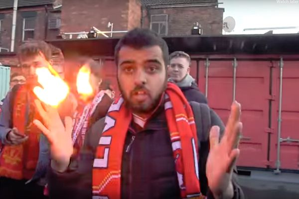 A Liverpool fan makes fire come out of his hands in a magic trick for a fan YouTube channel after a 2-0 win against Fulham at Anfield