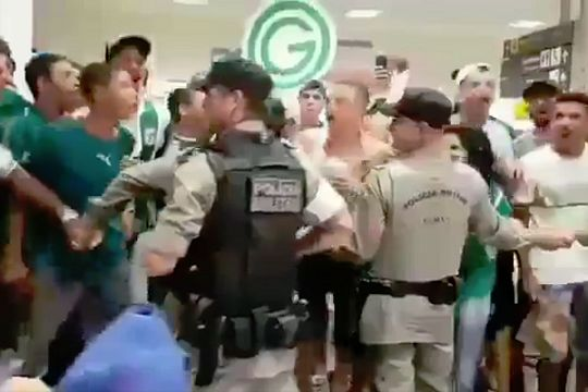 A police officer joins jumping Goiás fans waiting for the team at the airport