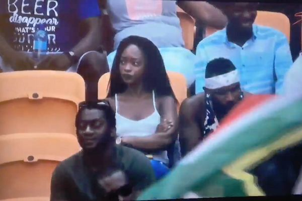 A woman hides after spotting herself on the television coverage of Jamaica vs Suriname