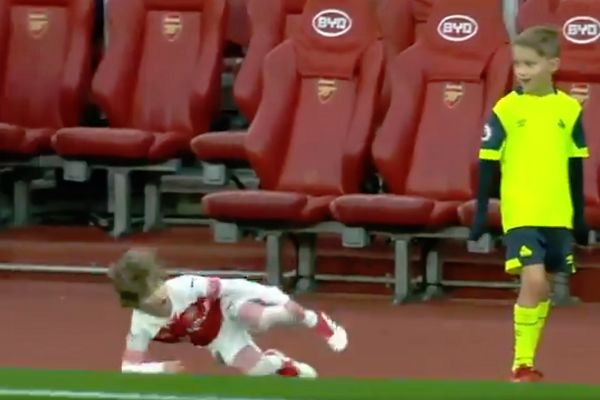 An Arsenal mascot rolls over and feigns injury after jumping on a Huddersfield mascot's back