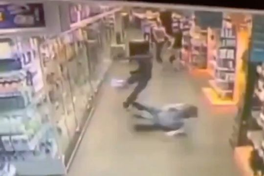 A shoplifter is slide tackled by a store employee