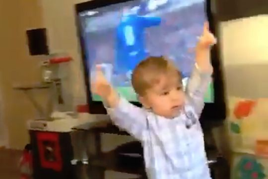 A boy celebrates Rangers' goal against Celtic while watching the game at home on TV